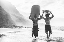 Multigeneration Friends Going To Surf On Tropical Beach - Family People Having Fun Doing Extreme Sport - Main Focus On Young Man Face - Black And White Editing