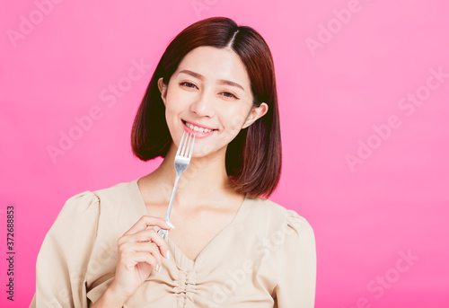 Foto Beautiful young woman holding a fork and tasting food