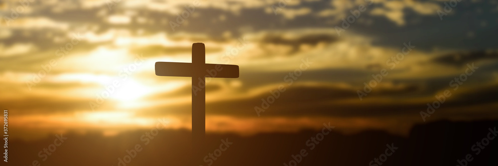 Fototapeta Silhouette of catholic cross at sunset background. panorama picture