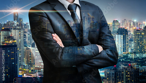 Fototapeta Double exposure of business man folded arms on city night background for success