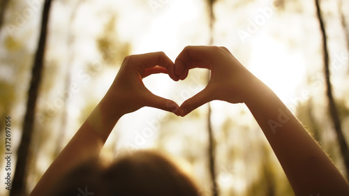Woman framing sun with her hands in heart shape Fototapete