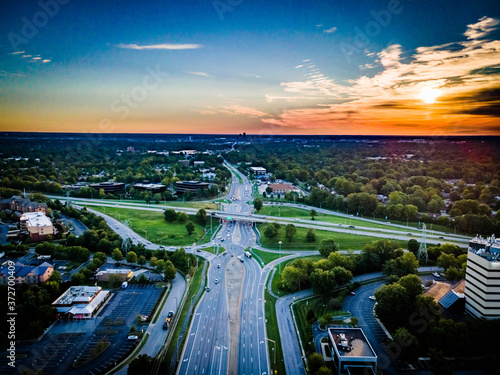 Fényképezés Red horizon during sunrise over eight shaped crossroad on Harrodsburg road in Lexington, Kentucky USA with distant view of city downtown