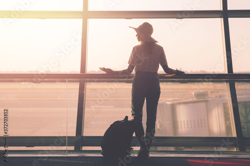 Canvastavla Airport, woman travel with hand luggage waiting for plane in terminal on backgro