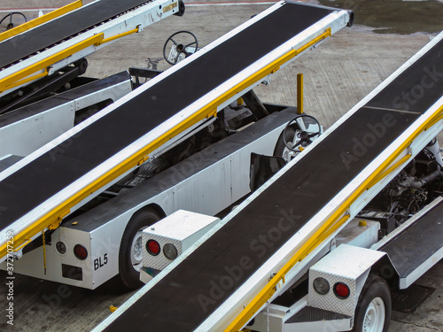 Photo Luggage conveyor vehicles in row at the airport