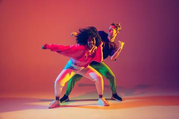 Vozite u pokretu. Moderan muškarac i žena plešu hip-hop u svijetloj odjeći na zelenoj pozadini u plesnoj dvorani u neonskom svjetlu. Kultura mladih, pokret, stil i moda, akcija. Moderan portret.
