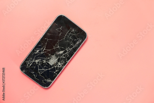 Fotografie, Obraz Top view of broken smart phone on color background