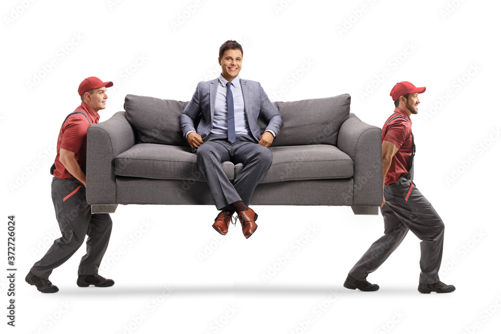 Fototapeta Smiling man in elegant clothes sitting on a sofa at home and two movers carrying the sofa