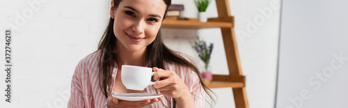 Obraz na plátně horizontal image of woman looking at camera while holding cup of coffee