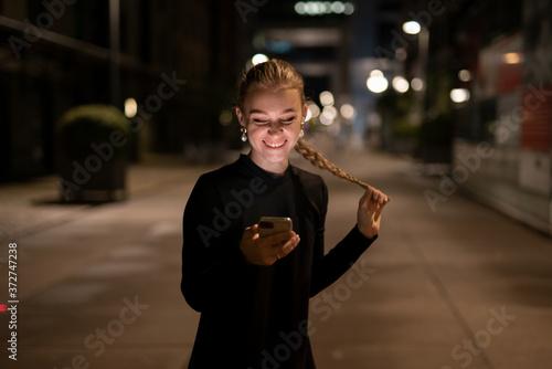 Lachende Junge Frau mit einem Smartphone in der Hand (Iphone 11 Pro) Lachende junge Frau mit einem Iphone 11 Pro in der Hand Fototapete
