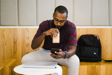 Man Drinking Iced Coffee And Looking At Smart Phone