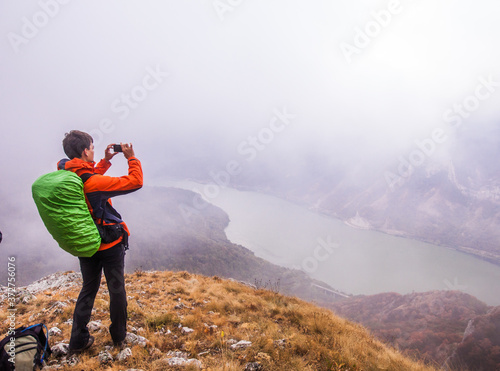 Obraz na plátně Man hiker on the mountain peak taking photo of Danube river landscape on foggy a
