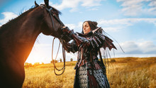 Girl In Medieval Knight's Armor With A Horse Against The Sunset Fields Background