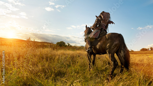 Foto Girl in medieval knight's armor is riding a horse against the sunset fields back