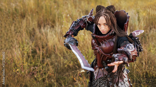 Fotografering Girl in medieval knight's armor with a big sword against the sunset fields backg