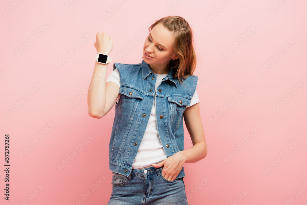 Fototapeta young woman in denim vest showing smartwatch on wrist while standing with hand in pocket isolated on pink