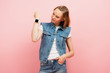 young woman in denim vest showing smartwatch on wrist while standing with hand in pocket isolated on pink