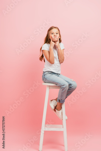 child in white t-shirt and blue jeans grimacing and puffing out cheeks while sit Wallpaper Mural