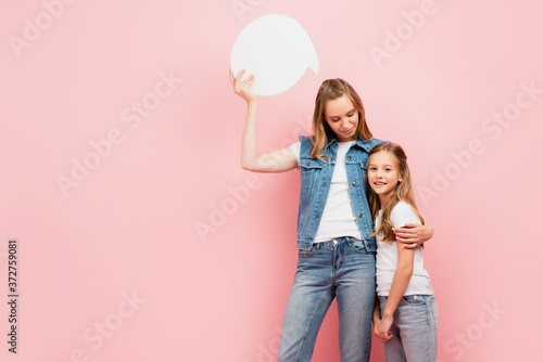 Fotografie, Obraz young woman in denim clothes holding thought bubble while hugging daughter isola