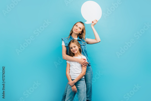 Fotografie, Tablou girl in white t-shirt and jeans looking at camera while mother holding thought b