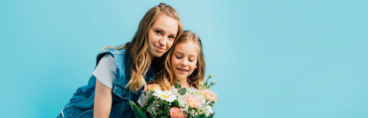 panoramic concept of young woman near daughter with bouquet of flowers isolated on blue