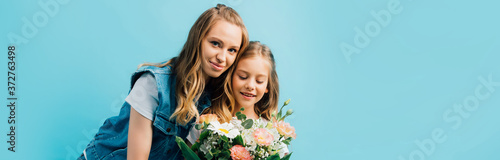 panoramic concept of young woman near daughter with bouquet of flowers isolated on blue #372763498