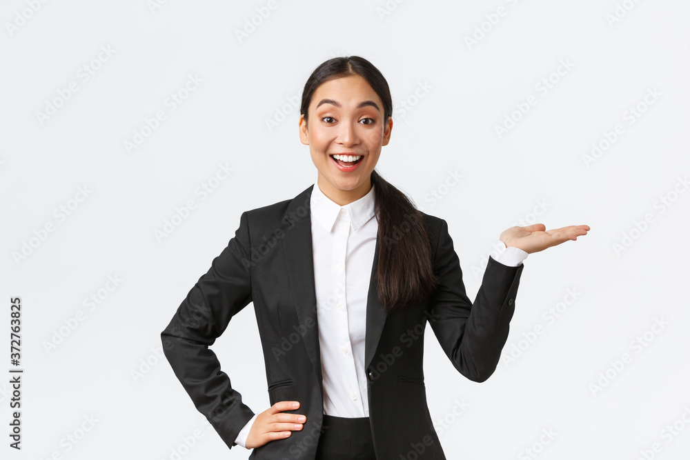 Fototapeta Excited smiling saleswoman introduce product, trying sell something over white copyspace. Pretty asian female manager showing project, pointing hand right and looking upbeat, white background