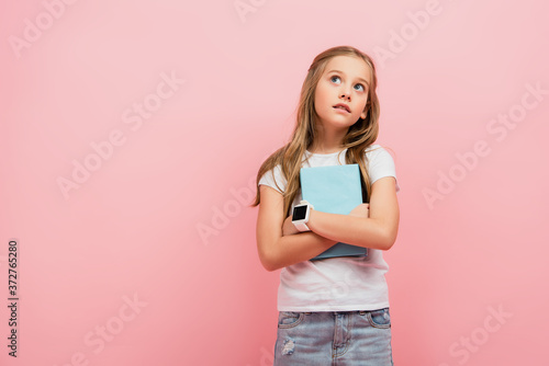 Fotografía thoughtful child in smartwatch looking away while holding book isolated on pink