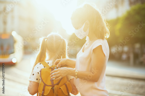 mother and school pupil getting ready for school outside Fototapete