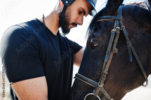 Tablou Canvas Arab tall beard man wear in black helmet with arabian horse.