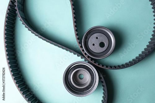Obraz na plátně New set of timing belt and idler pulleys on a blue background.