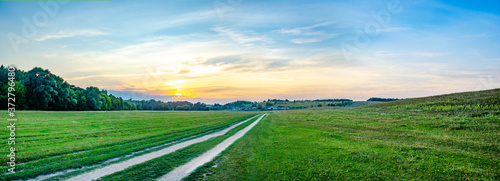 Fototapeta wide panorama with sunset over the field