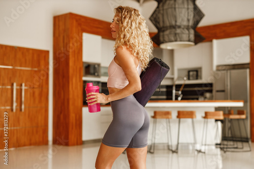 Stampa su Tela A sporty woman in workout tight suit is holding  yoga mat and starting to drink