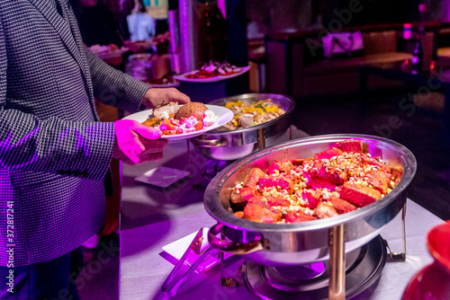 Fotografiet Male taking food from buffet pans full of different tasty dishes