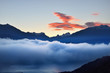 Leinwanddruck Bild - Mountain peaks in a morning fog at sunrise. Clear colorful sky with glowing clouds, pure sunlight. Epic cloudscape. French Alps, Ecrins massif, France