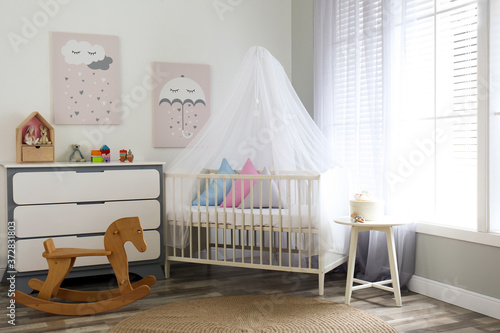 Obraz na plátně Baby room interior with cute posters, chest of drawers and comfortable crib