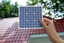 Woman Holding Solar Panel Near Building Outdoors, Closeup