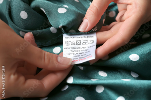 Fotografie, Obraz Woman reading clothing label with care instructions and content information on g