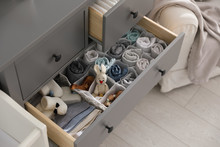Modern Open Chest Of Drawers With Clothes And Accessories In Baby Room