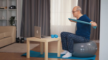 Old Man On Balance Ball Training With Resistance Band Watching Online Fitness Program. Old Person Pensioner Healthy Training Healthcare Sport At Home, Exercising Fitness Activity At Elderly Age