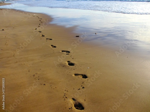 Photo Human footsteps on wet sand at the very edge of the surf