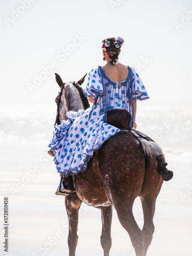 Tablou Canvas Beautiful shot of Caucasian female riding a horse at the beach of Matalascanas,