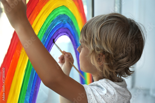 Little boy drawing rainbow on window. Stay at home concept