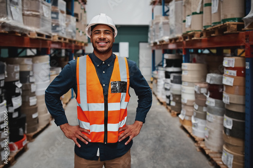 Fotografia Portrait of successful manager standing in warehouse between shelf filled with g