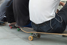 Young Skateboarders Sit On Sports Equipment
