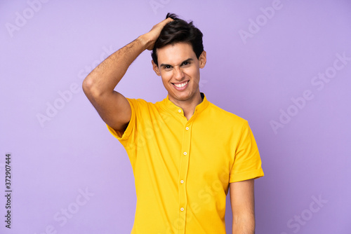 Fototapeta Man over isolated purple background with an expression of frustration and not un