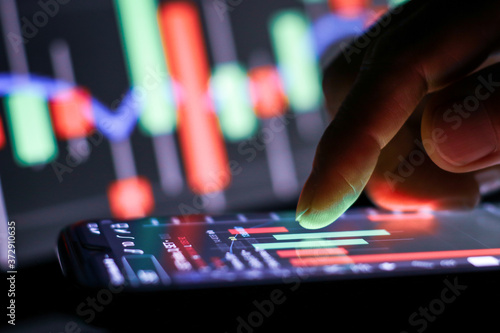 Canvastavla Businessman finger touching screen on smartphone with stock market graph at night