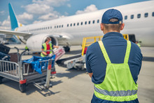 Baggage Handlers Loading Suitcases Onto An Airplane