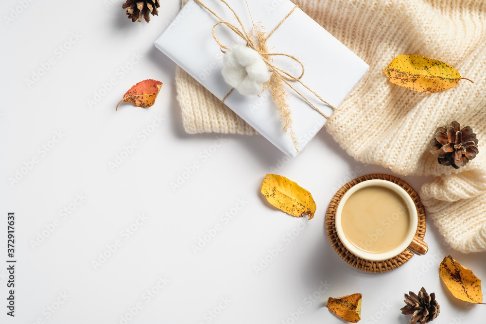 Fototapeta Autumn flat lay composition. Knitted plaid, gift box wrapped eco-friendly wrapping paper, coffee cup, fallen leaves, pine cones on white table. Autumn, fall concept.