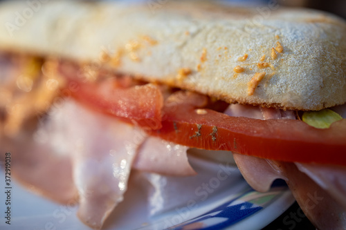 Carta da parati elective focus close up of a mouth watering, rich italian home made sandwich with genuine ingredients like mortadella ham, tomato slices and a sauce