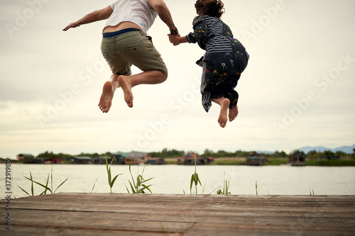 Stampa su Tela Young couple in love jumping on the shore of the lake